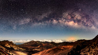 Milky Way and Kiluaea volcano lava flow glow over moonlit Haleakala Crater in Maui